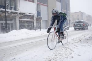 person delivering parcel in ottawa snow on bicycle